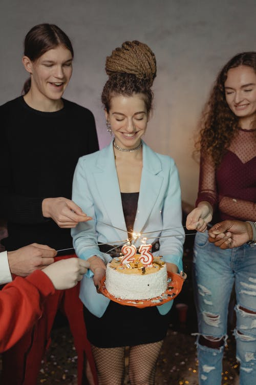 Man in White Suit Jacket Holding Cake With Lighted Candles