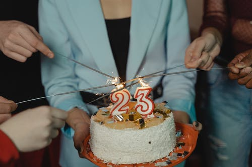 Person in White Blazer Holding Brown Cake With Red and White Icing