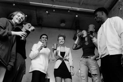 Grayscale Photo of 3 Men and Woman Holding Microphone