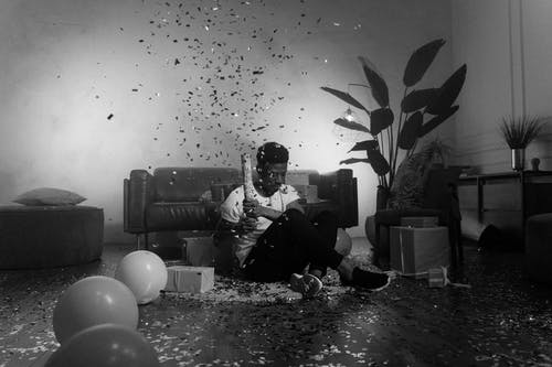 Man in Black Jacket Sitting on Floor With Balloons