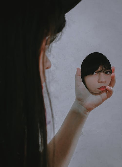 Crop serious ethnic female with long hair and red lips reflecting in small hand mirror