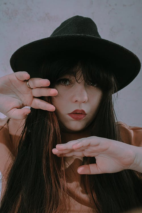 Charming young female with red lips in trendy hat raising hands to face and looking at camera