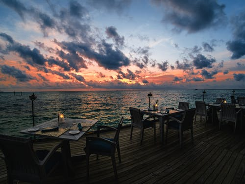 Black Wooden Table and Chairs on Wooden Dock during Sunset