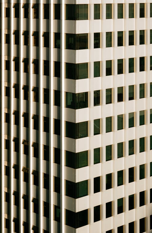 Background of high rise building with rows of white panels and windows in daylight