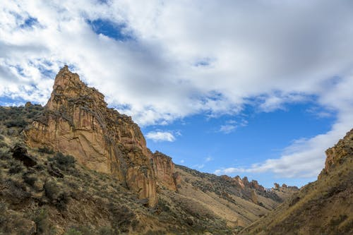 Rough stony terrain of peak among mountains under bright blue sky with cumulus clouds