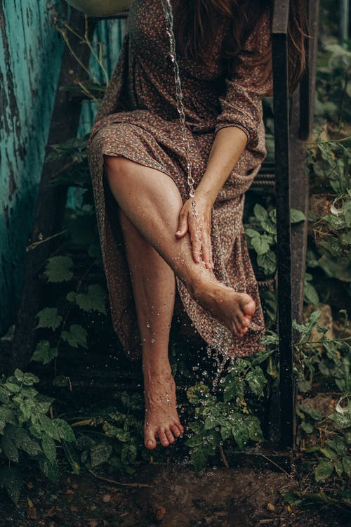 Crop faceless barefoot female washing legs with clear water while sitting on metal staircase overgrown with greenery