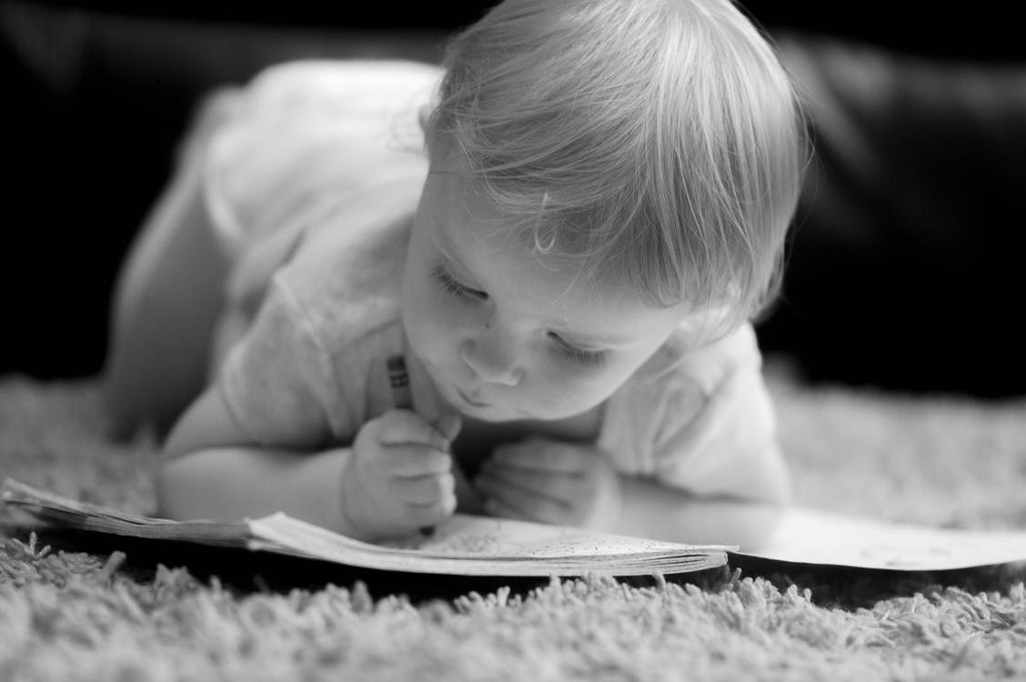 Grayscale Photo of Baby Scribbling on Notebook