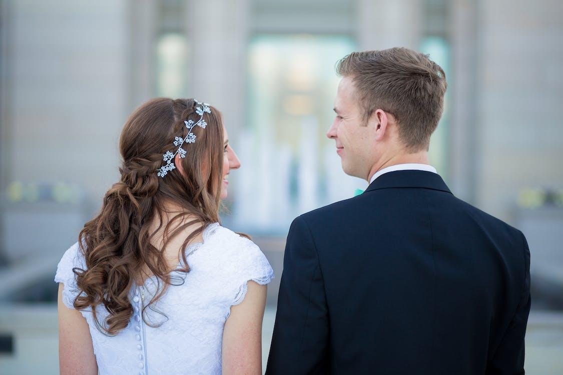 Man Standing Beside Woman Wearing White Cap-sleeved Dress