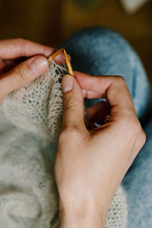 From above of crop anonymous woman creating handmade gray sweater with needles and woolen yarn while sitting at home