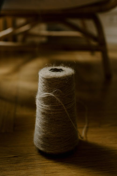 Big spool of gray woolen thread used for knitting located on wooden floor near chair in cozy apartment