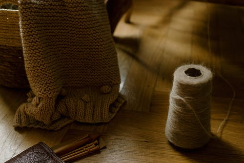 Handmade knitted blanket on wicker basket near needles and spool of thread