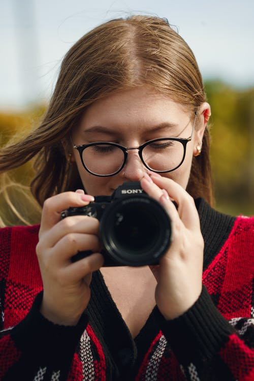 Young female in eyeglasses using modern photo camera standing on blurred background of nature