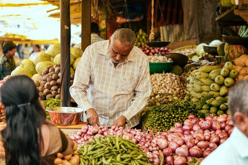 Ethnic seller working at local bazaar with vegetables