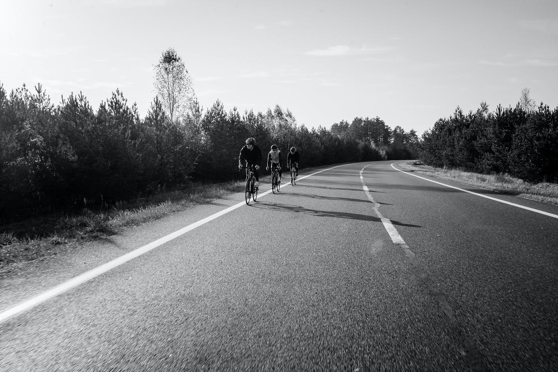 Grayscale Photo of Three People Biking on the Road