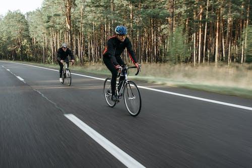 Two People Biking on the Road
