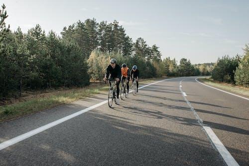 Three People Biking on the Road
