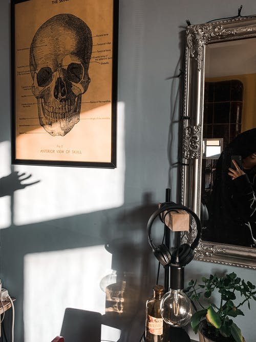 Old fashioned lamp and headphones placed at wall with mirror and picture of skull in room with bright sunlight at home