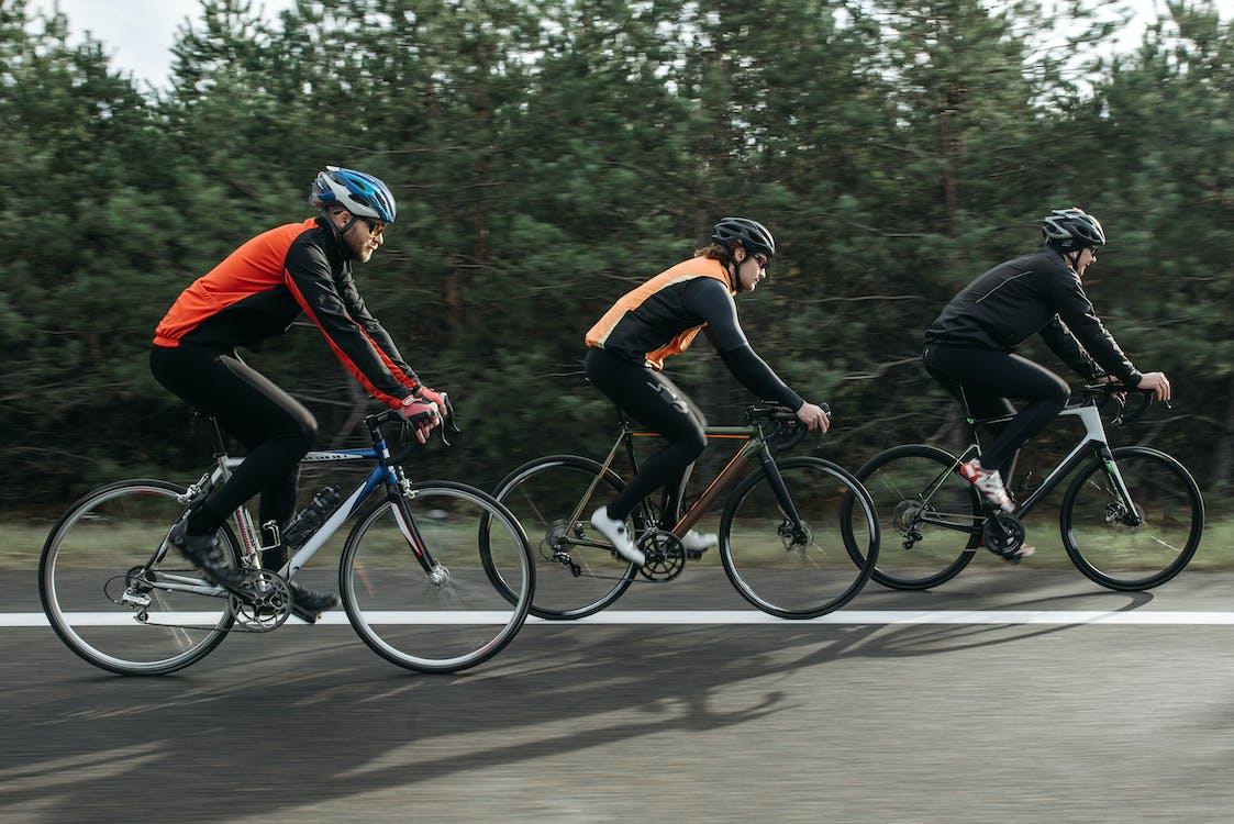 Man in Orange and Black Shirt Riding on Black Bicycle