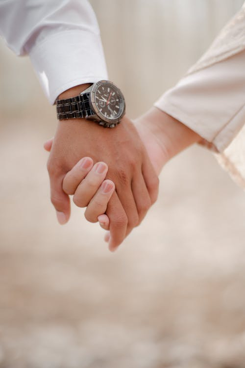 A Close-Up Shot of a Man and a Woman Holding Hands