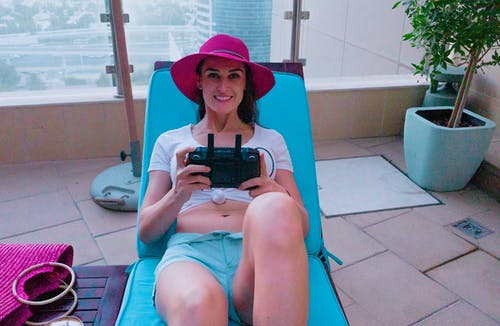 Woman in Blue Shorts and Red Hat Sitting on Red and White Lounge Chair