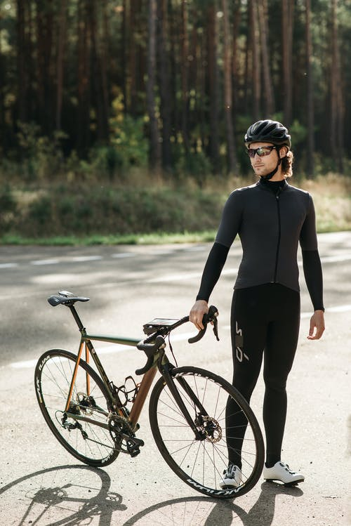 Woman in Black Long Sleeve Shirt and Black Pants With Black and Red Bicycle on Road