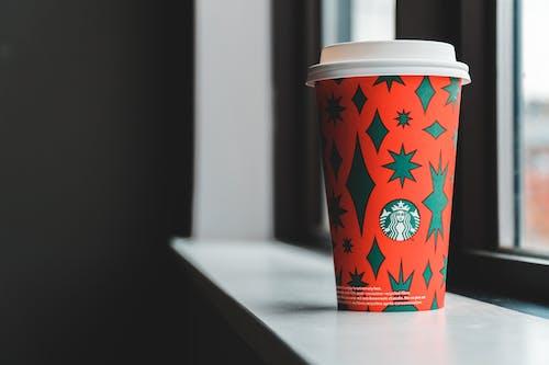 Cup of takeaway coffee placed on windowsill