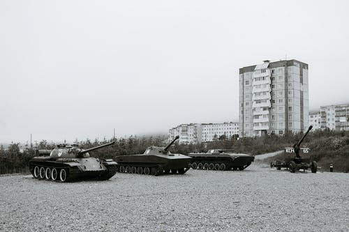 Black and white of monuments of various military vehicles on square in city
