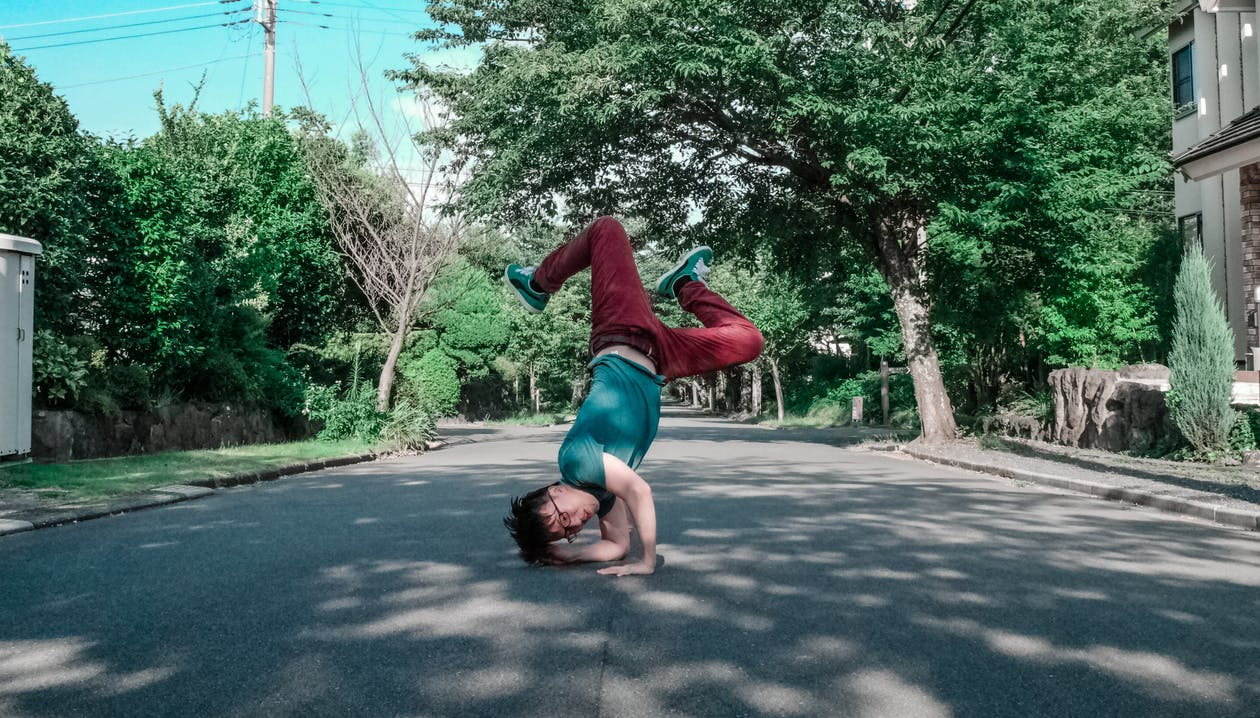 Man Doing Head Stand on Road
