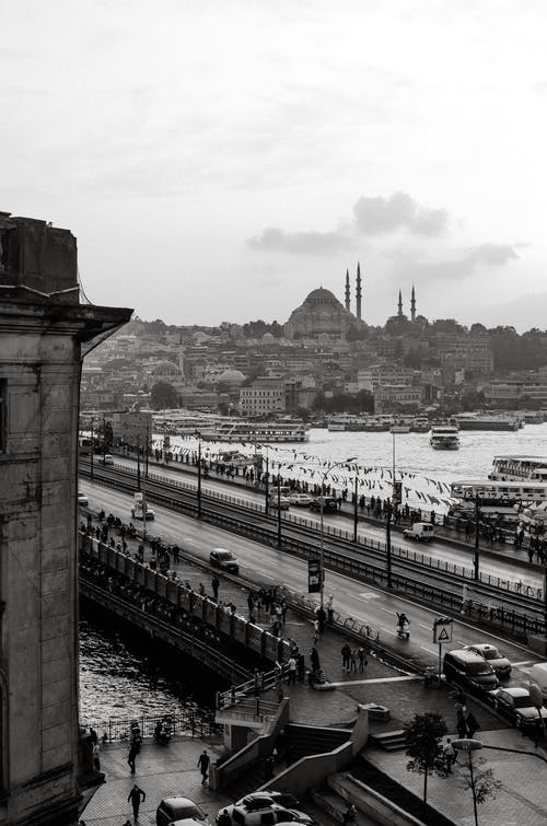 Black and white of amazing cityscape of Istanbul with bridge over river and Hagia Sophia Holy Grand Mosque against cloudy sky