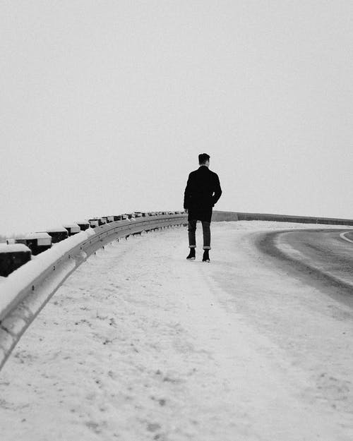 Man in Black Jacket Walking on Snow Covered Road