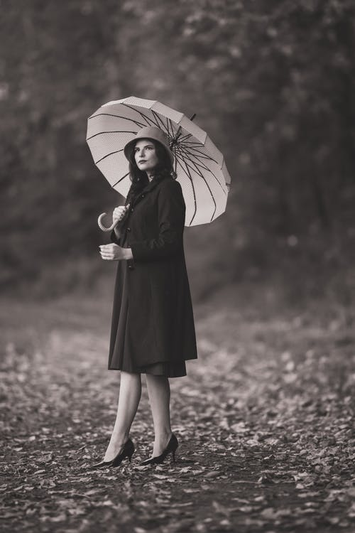 Grayscale Photo of Woman in Black Dress Holding Umbrella