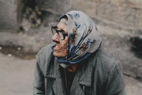 Elderly ethnic woman in eyeglasses on street