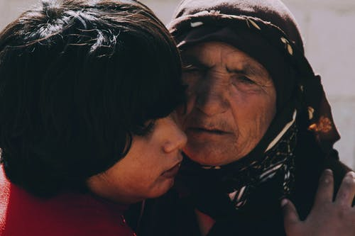 Crop ethnic child embracing unhappy elderly grandma in headscarf while looking away in sunlight