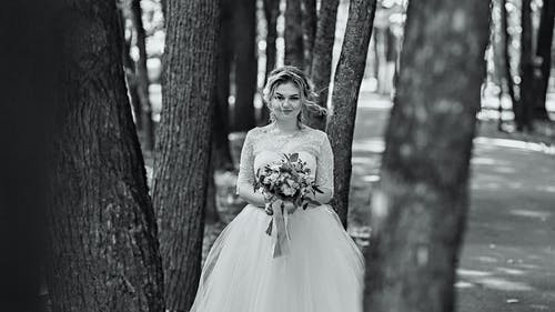 Happy newlywed young woman standing among high trees
