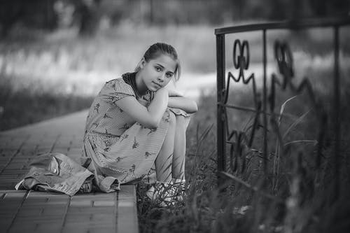 Girl in Striped Dress Sitting on Curb With Her Arms on Knees