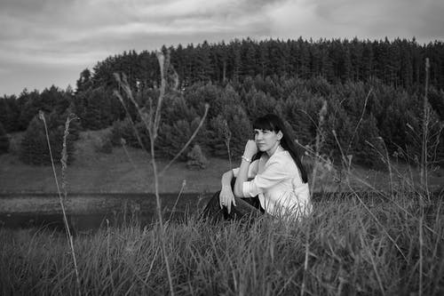 Black and white of young dreamy woman wearing white shirt sitting on grassy field of wide river flowing near forest on cloudy day