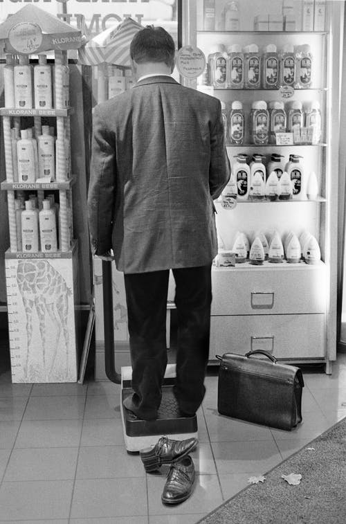 Faceless barefoot man standing on scale in store