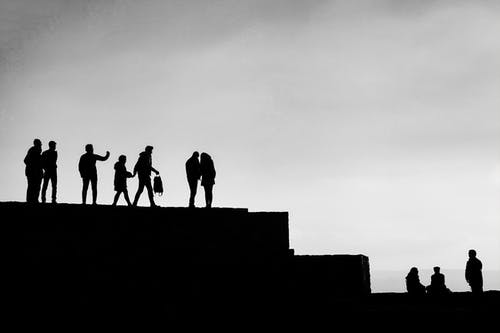 Black and white of group of people resting on stone border and enjoying picturesque view
