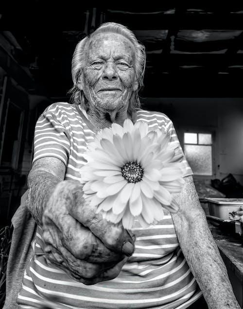 An Elderly Woman Holding a Flower