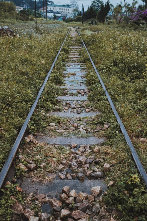 Railroad tracks on green grass in daytime