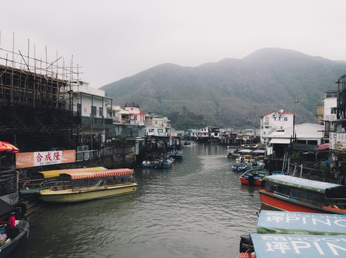 Moored boats near residential buildings of floating village