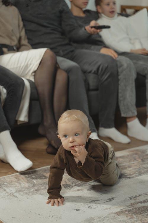 Boy in Brown Jacket Sitting on Floor