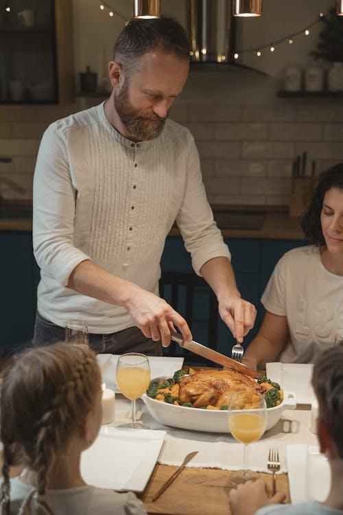 A Man Cutting a Turkey on the Dinner Table