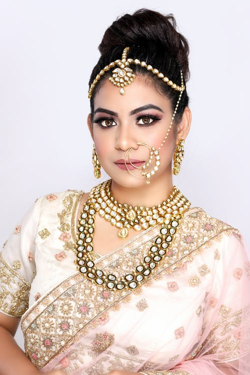 Elegant Indian female wearing traditional sari with nathi nose ring and luxury accessories looking at camera