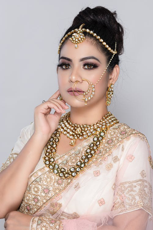 Unemotional Indian woman wearing elegant traditional sari with golden accessories touching face gently against gray background