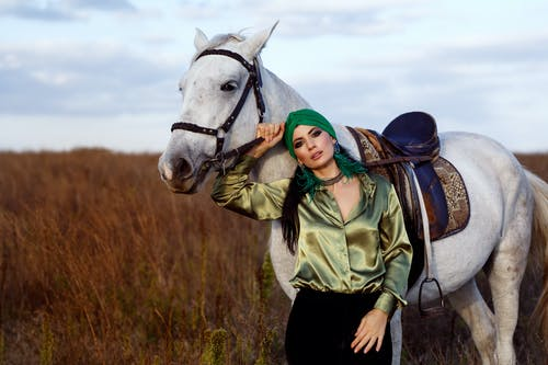 Elegant female equestrian in turban standing near horse with saddle in grassy valley and looking at camera
