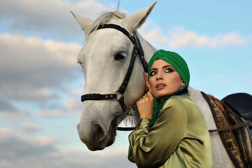 Low angle side view of dreamy ethnic female with makeup holding bridle of horse with saddle under clouds and looking away