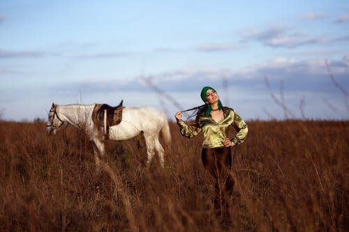 Smiling ethnic woman in grassy terrain near horse