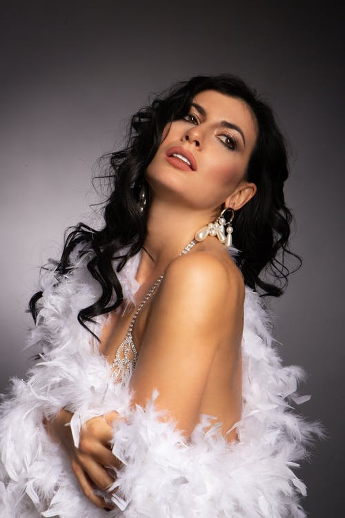 Side view of sensual female model wearing shiny bra and earrings wrapped in feather boa