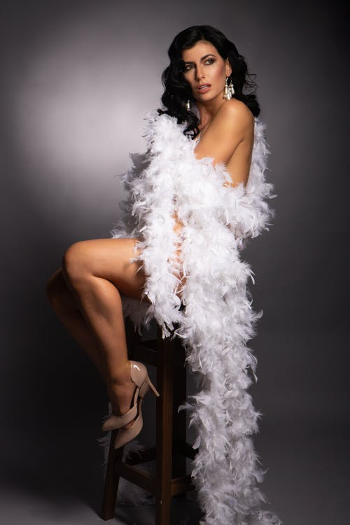 Naked woman wrapped in feather boa in studio